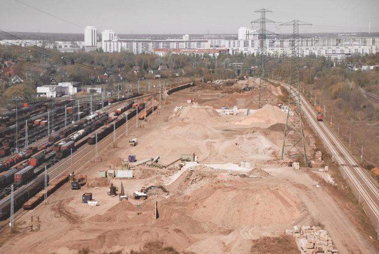 Luftaufnahme vom BTB Recyclinghof Berlin neben Bahngleisen, im Hintergrund das Neubaugebiet Hohenschönhausen