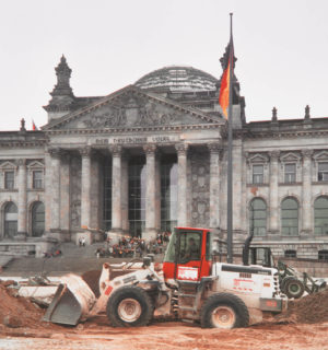 BTB excavator in front of the Berlin Reichstag building excavating earth