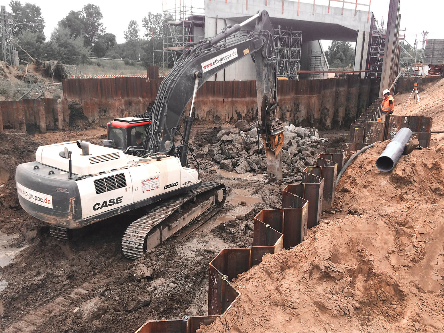 A heavy construction machine with a hammer demolishing an old embankment and old bridges