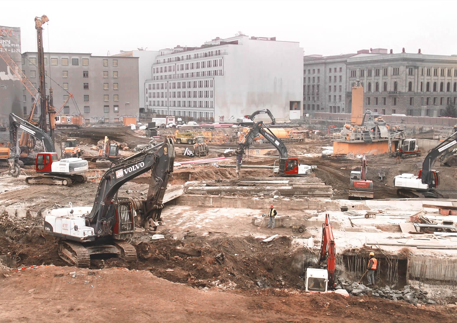 meherere schwere Baugeräte mit Sägen, Hämmern und Schaufeln tragen Betondecken der U-Bahn für den Bau der Mall of Berlin ab