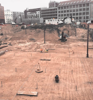 Excavation pit with several construction machines and construction workers for the new building of the Axel Springer publishing house in Berlin