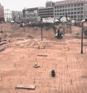 Baugrube mit mehreren Baugeräten und Bauarbeitern für den Neubau des Axel-Springer-Verlags in Berlin