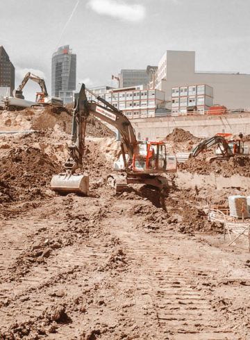 Excavation pit of the Mall of Berlin with several excavators and trucks, in the background the DB building at Postdamer Platz.