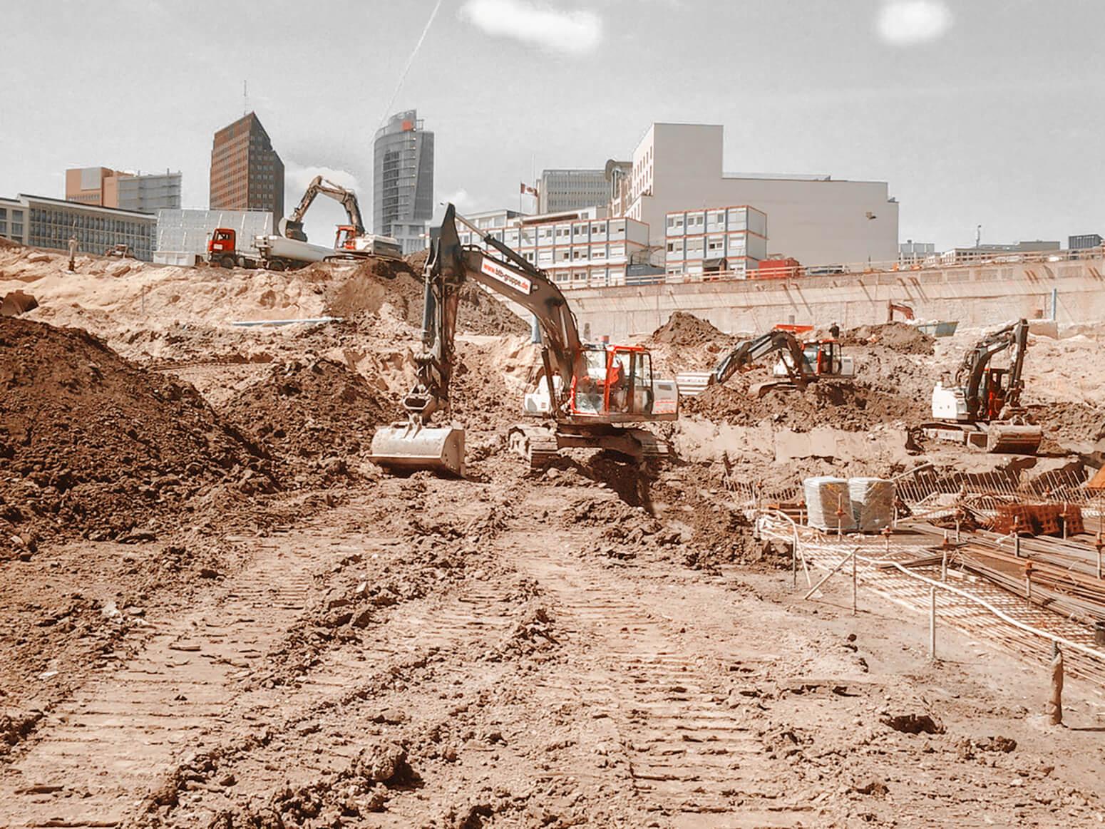 Baugrube der Mall of Berlin mit mehreren Baggern und LKW, im Hintergrund das DB Gebäude am Postdamer Platz