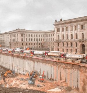 Baugrube für die Mall of Berlin mit mehreren Baggern und einem Kran, mehre LKW warten zur Abfuhr des Erdaushubs am Rand