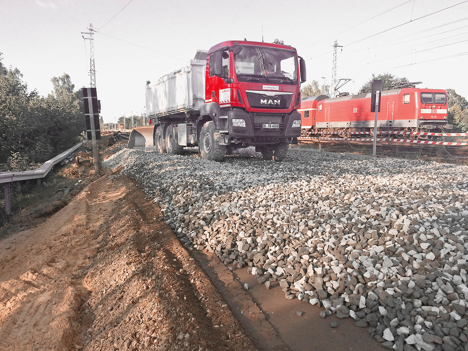 A BTB dumper truck on a freshly prepared gravel bed with a DB S-Bahn (city train) and railway tracks in the background