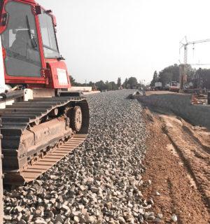 eine Walze von BTB bringt Bahnschotter für einen neuen Bahndamm auf
