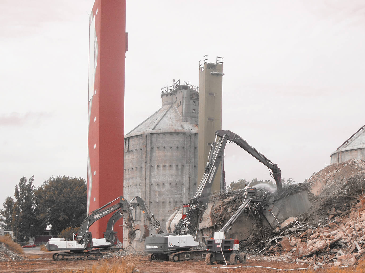 Several heavy construction vehicles tear down buildings made of reinforced concrete with two old digester towers in the background