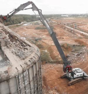 Luftaufnahme des Abrisses eines hohen Gebäudes durch eine schwere Baumaschine