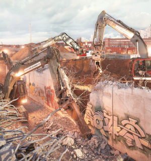 Several heavy construction machines demolish a reinforced concrete tunnel late in the evening