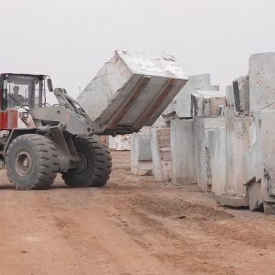 Eine schwere Baumaschine befördert große Betonblöcke