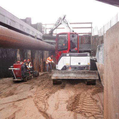 ein kleiner Bagger hebt Boden unter sehr engen Platzverhältnissen zwischen Spundwänden aus, mehrere Bauarbeiter