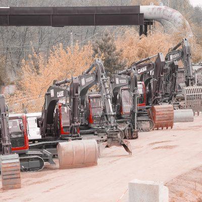mehrere Baumaschinen von BTB mit verschiedenen Anbauteilen, Schaufeln und Gabeln stehen in einer Reihe, Im Hintergrund Bahngleise