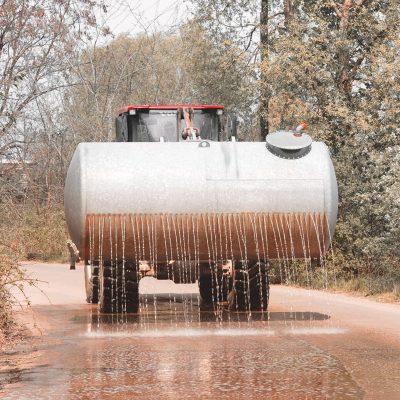 eine Baumaschine wässert zur Staubbindung den Boden